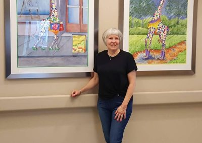 Rhonda Leonard standing with two of her paintings